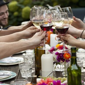 Group of friends gathered around a table, clink their glasses.